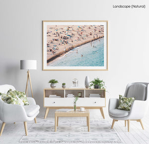 People lying on beach along calm blue sea in a natural fine art frame