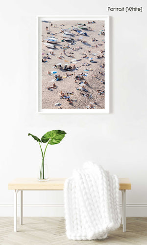 Crowd of people lying on sand next to boats in a white fine art frame