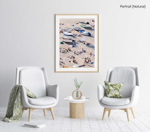 People lying on sand next to boats in a natural fine art frame