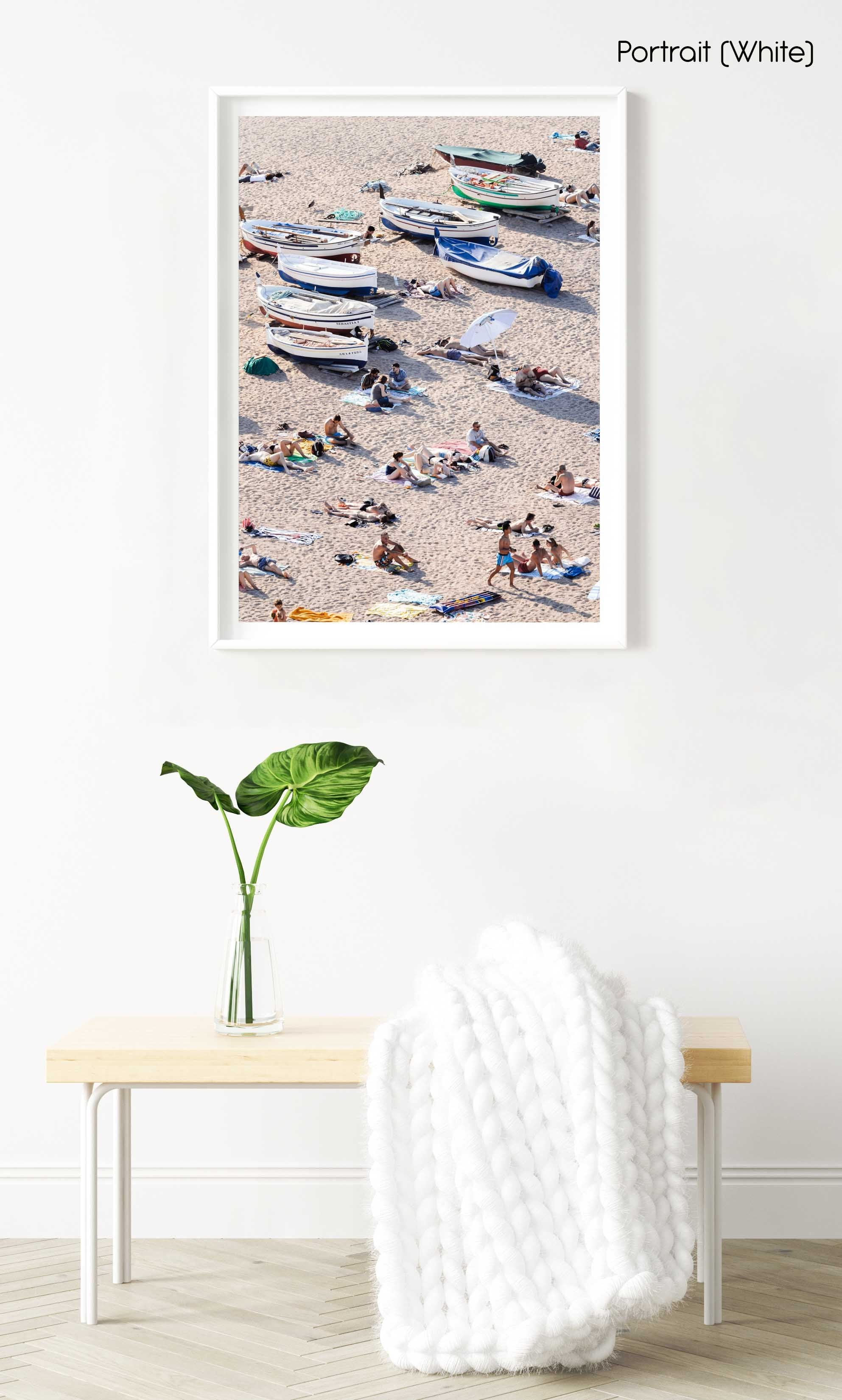 People lying on sand next to boats in a white fine art frame