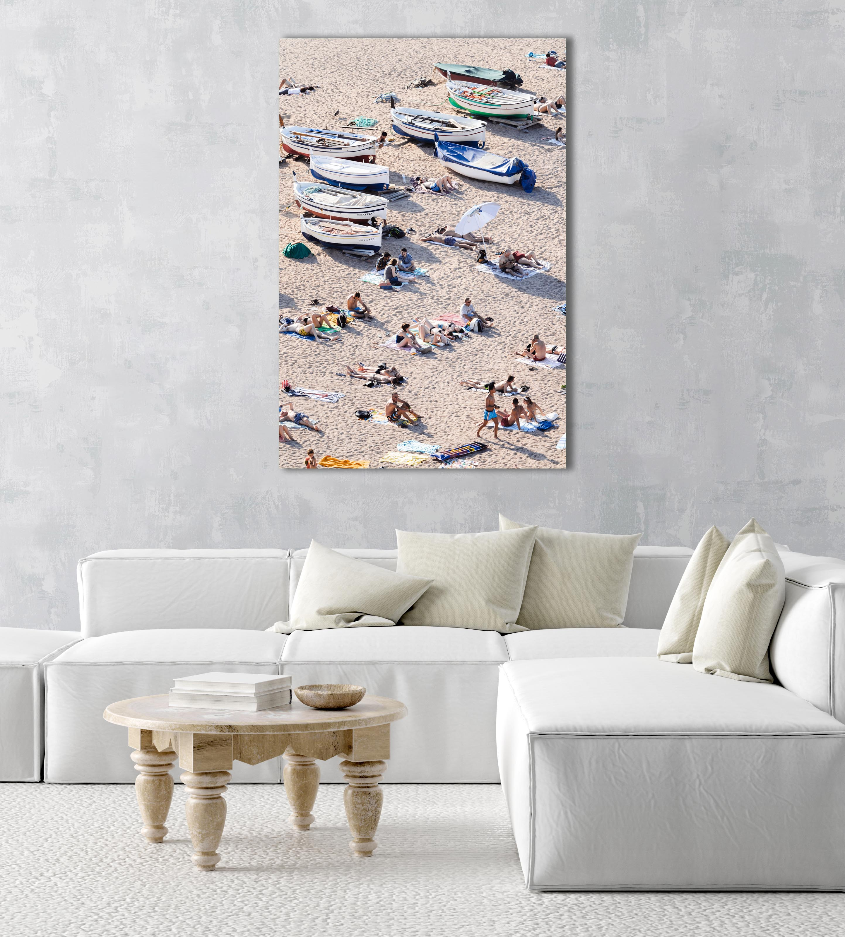 People lying on sand next to boats in an acrylic/perspex frame