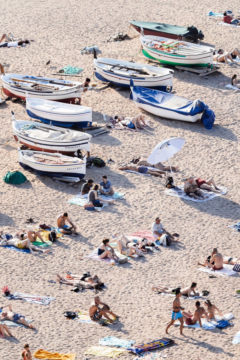 People lying on sand next to boats