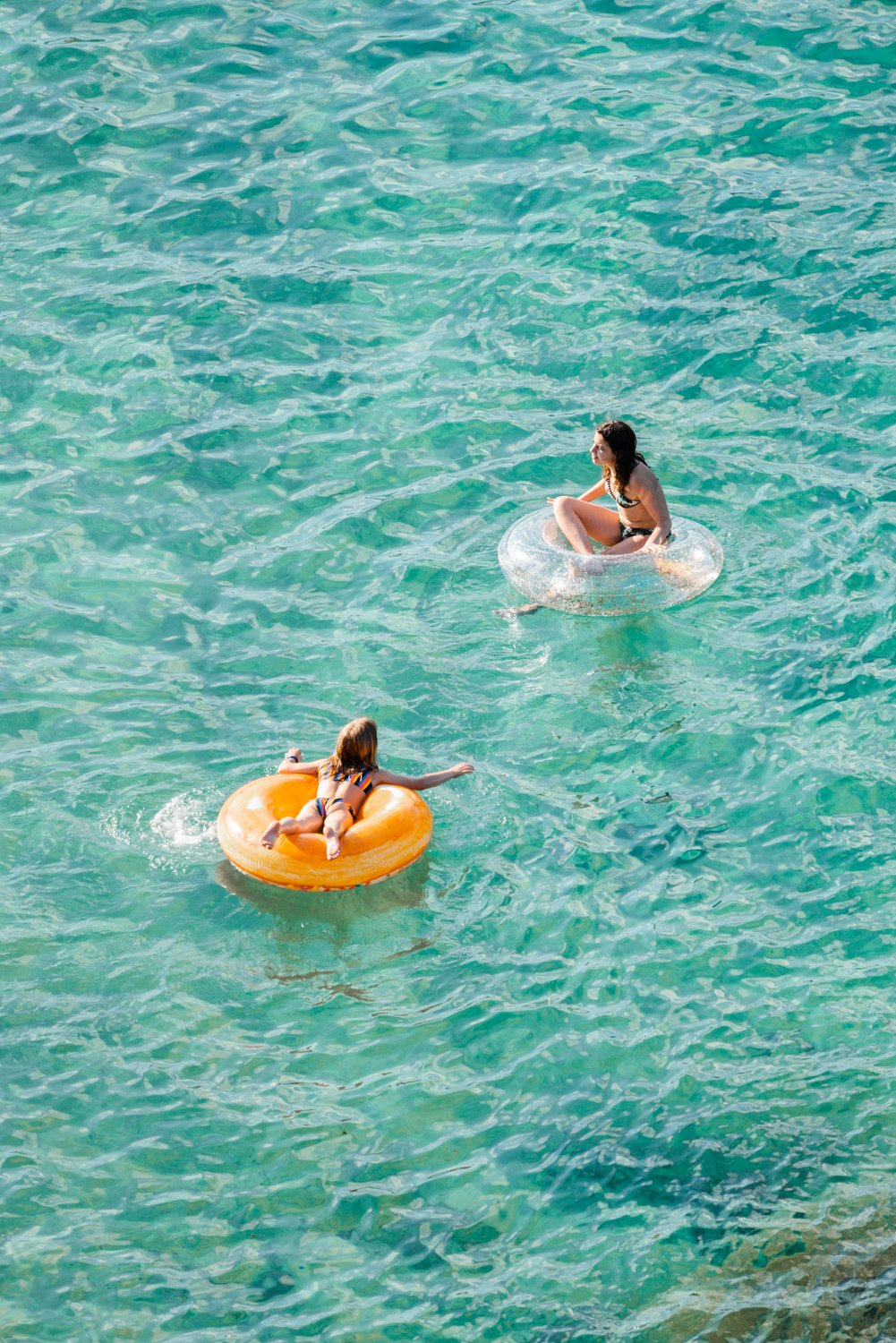 Young girl and woman floating on round lilos in turquoise sea