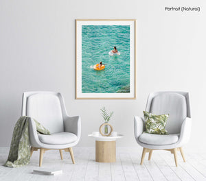 Young girl and woman floating on round lilos in turquoise sea in a natural fine art frame