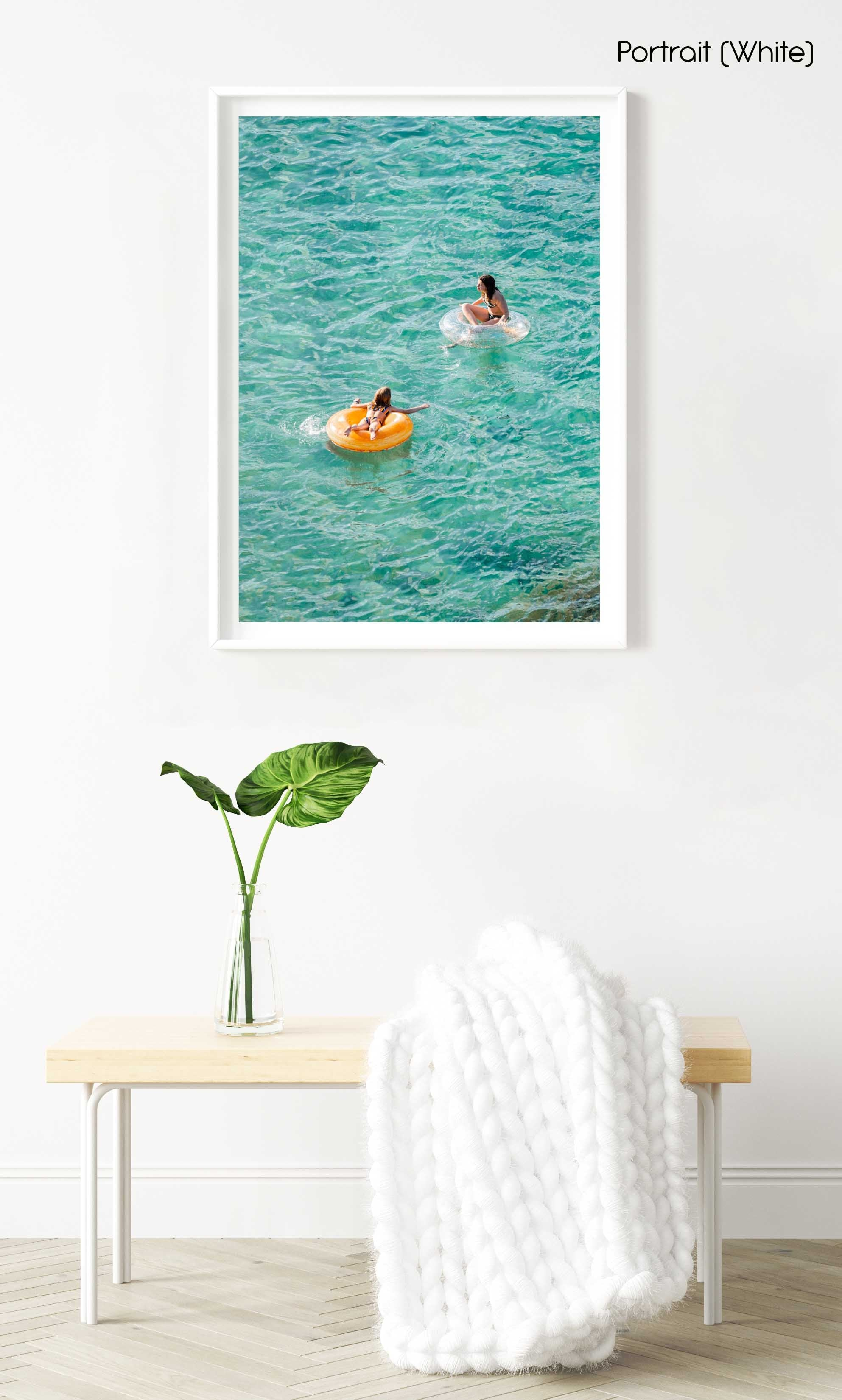 Young girl and woman floating on round lilos in turquoise sea in a white fine art frame