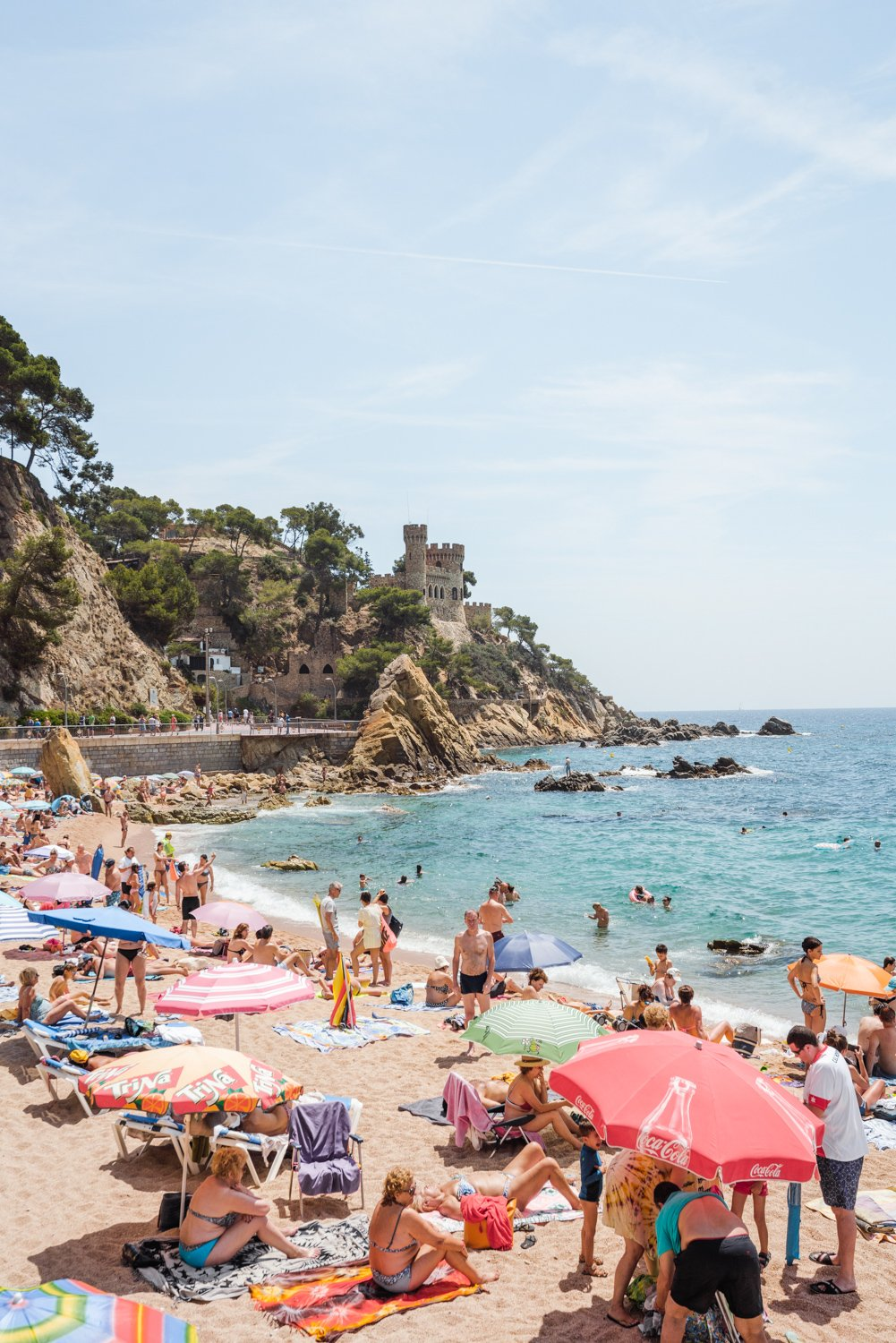 Umbrellas, people on sand and a castle along Costa Brava