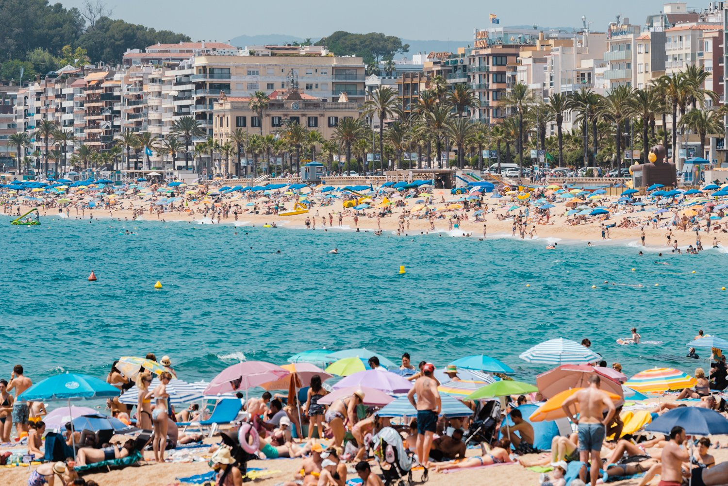 Crowds of people on either side of beaches at Lloret de Mar in a white fine art frame