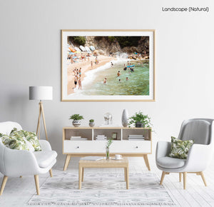 Swimmers, divers and people lying at beach with green water and colorful boats in a natural fine art frame