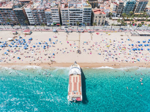 Big boat parked off on Lloret de Mar beach from above