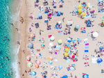 Very crowded Lloret de Mar beach from above with blue water, colorful towels and umbrellas