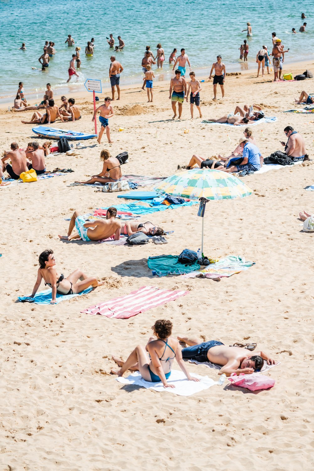 People tanning, swimmers and umbrellas at a beach in Cascais Portugal