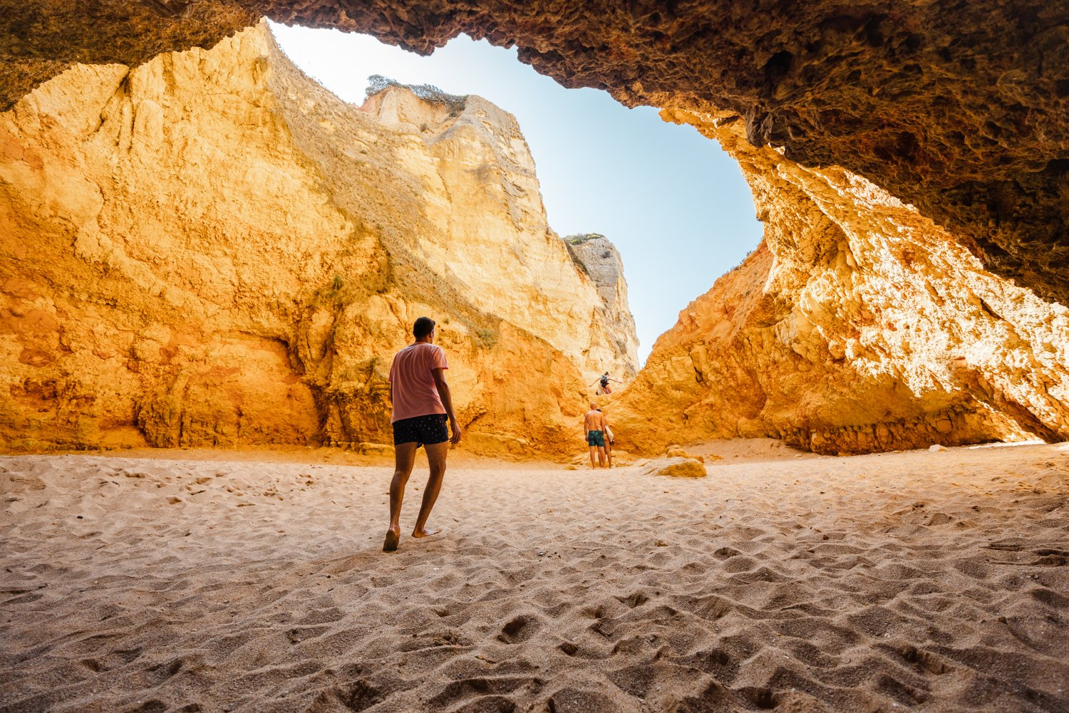 Man walking in a big yellow cave in Praia Dona Ana beach in Lagos