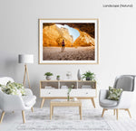 Man walking in a big yellow cave in Praia Dona Ana beach in Lagos in a natural fine art frame
