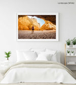 Man walking in a big yellow cave in Praia Dona Ana beach in Lagos in a white fine art frame