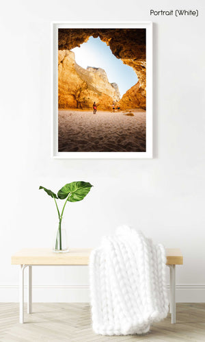 Man in red shorts standing in a big cave in Lagos in a white fine art frame