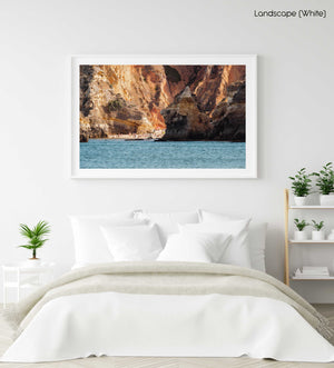 People tucked away under cliffs in Lagos and blue sea in a white fine art frame