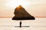 Orange sunrise with woman paddling on a SUP near a big rock in Lagos