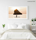 Orange sunrise with woman paddling on a SUP near a big rock in Lagos in a white fine art frame