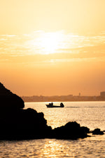 Orange sunrise with a boat cruising past Lagos coastline