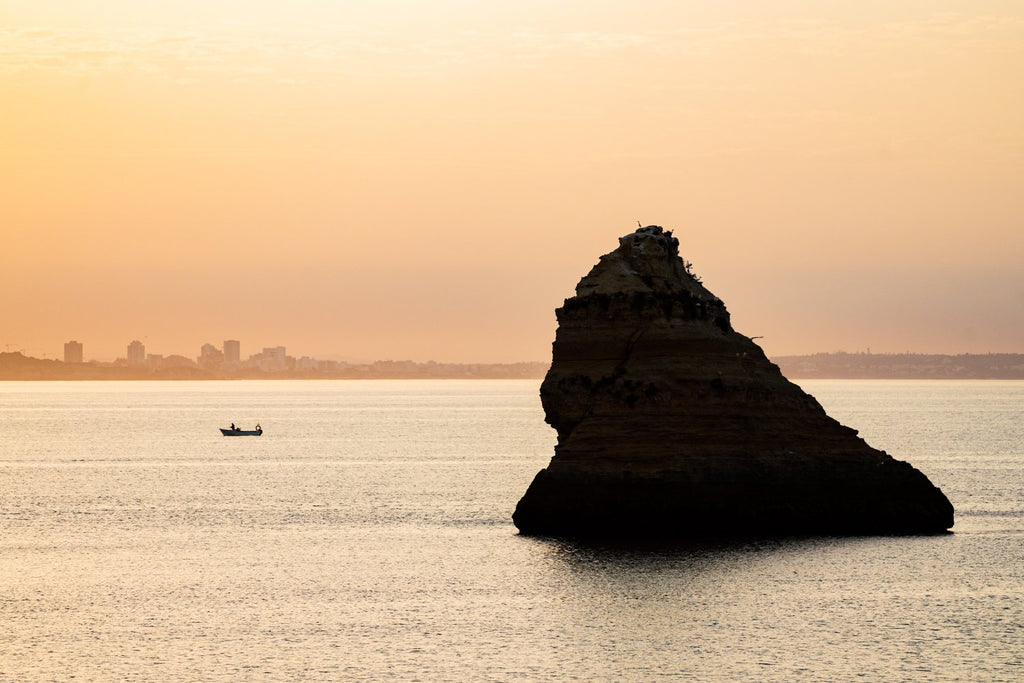 Large boulder and a fishing boat during Lagos sunrise