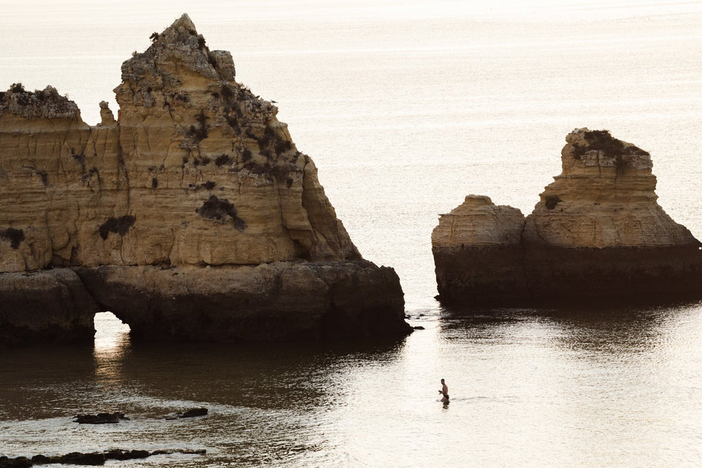 Man swimming during sunrise near large cliffs in Lagos