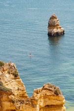 Woman on a SUP in the ocean along Lagos blue water and cliffs