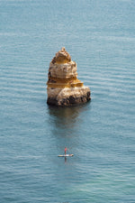 Woman on a SUP paddling near big cliff in Lagos