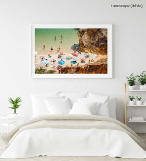 Crowd of people lying with umbrellas and swimming in green sea on Camilo beach in a white fine art frame
