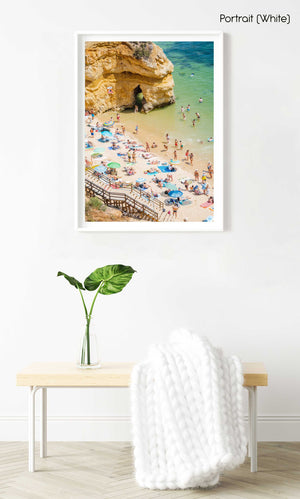 Stairway leading down to people, umbrellas, sand and green water on Camilo beach in a white fine art frame