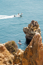 Two people on SUP watching boat drive past Lagos cliffs