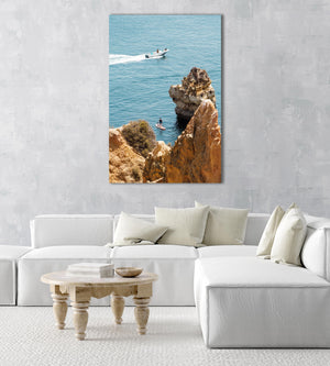 Two people on SUP watching boat drive past Lagos cliffs in an acrylic/perspex frame