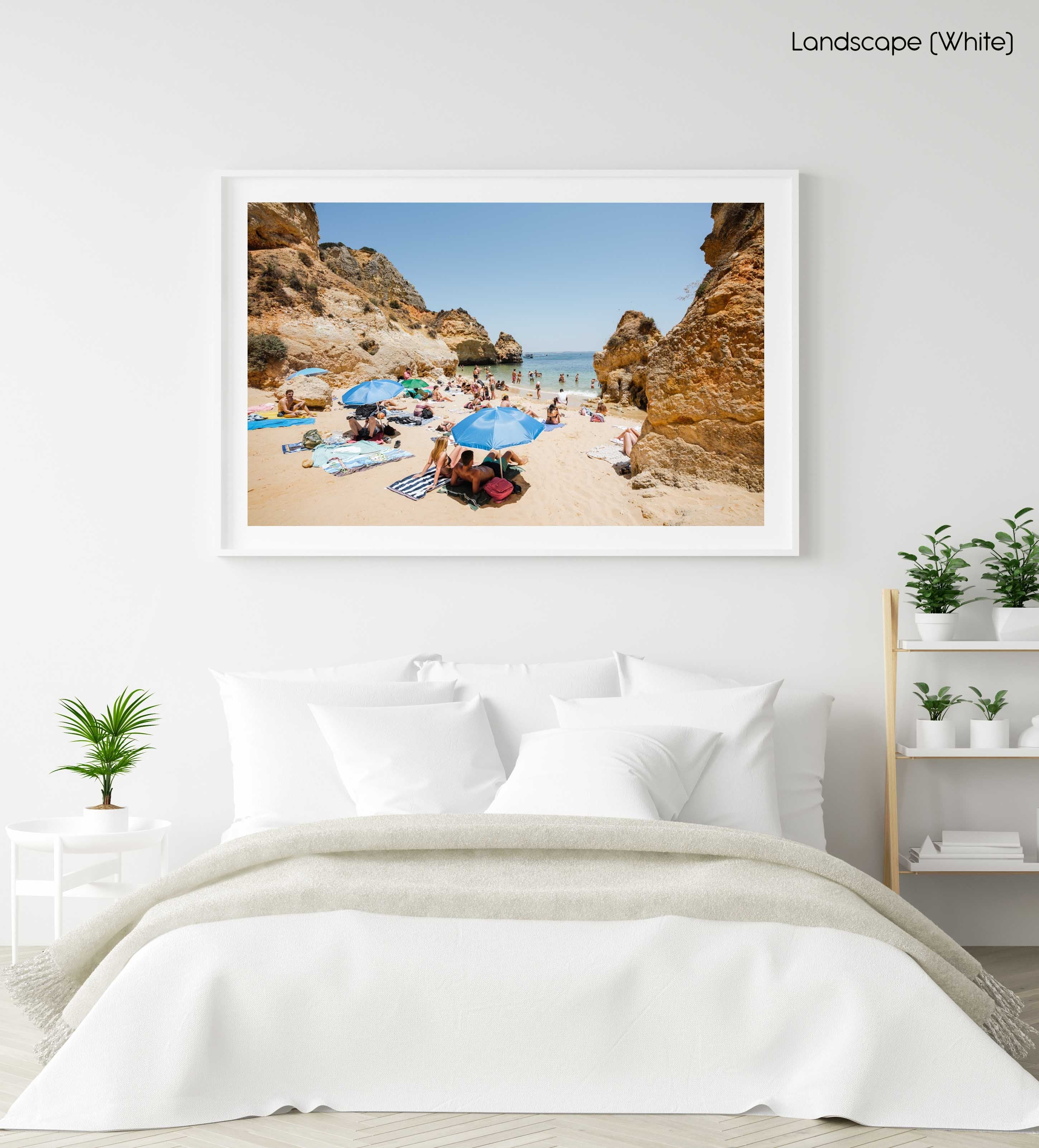 Blue umbrellas and people on Camilo beach Portugal in a white fine art frame