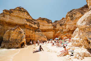 High cliffs overhanging beach where people lying under in June