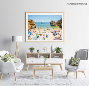 Busy Camilo beach with cliffs, people and calm green water in a natural fine art frame