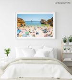 Busy Camilo beach with cliffs, people and calm green water in a white fine art frame
