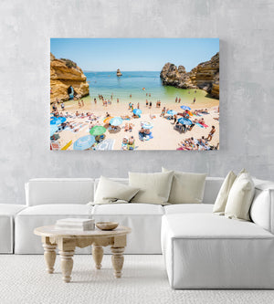 Busy Camilo beach with cliffs, people and calm green water in an acrylic/perspex frame
