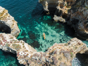 Aerial of two people paddling yellow kayak near Lagos caves in ocean