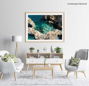 Aerial of two people paddling yellow kayak near Lagos caves in ocean in a natural fine art frame