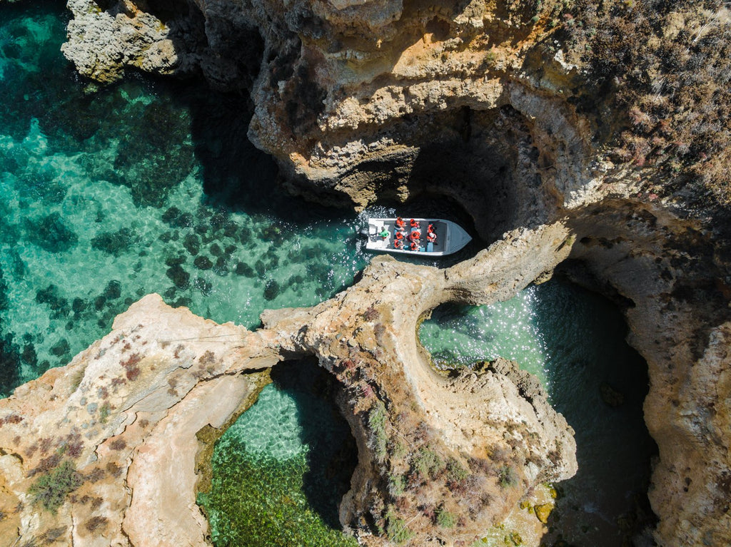 Aerial of a tour boat in caves along Ponta da Piedade