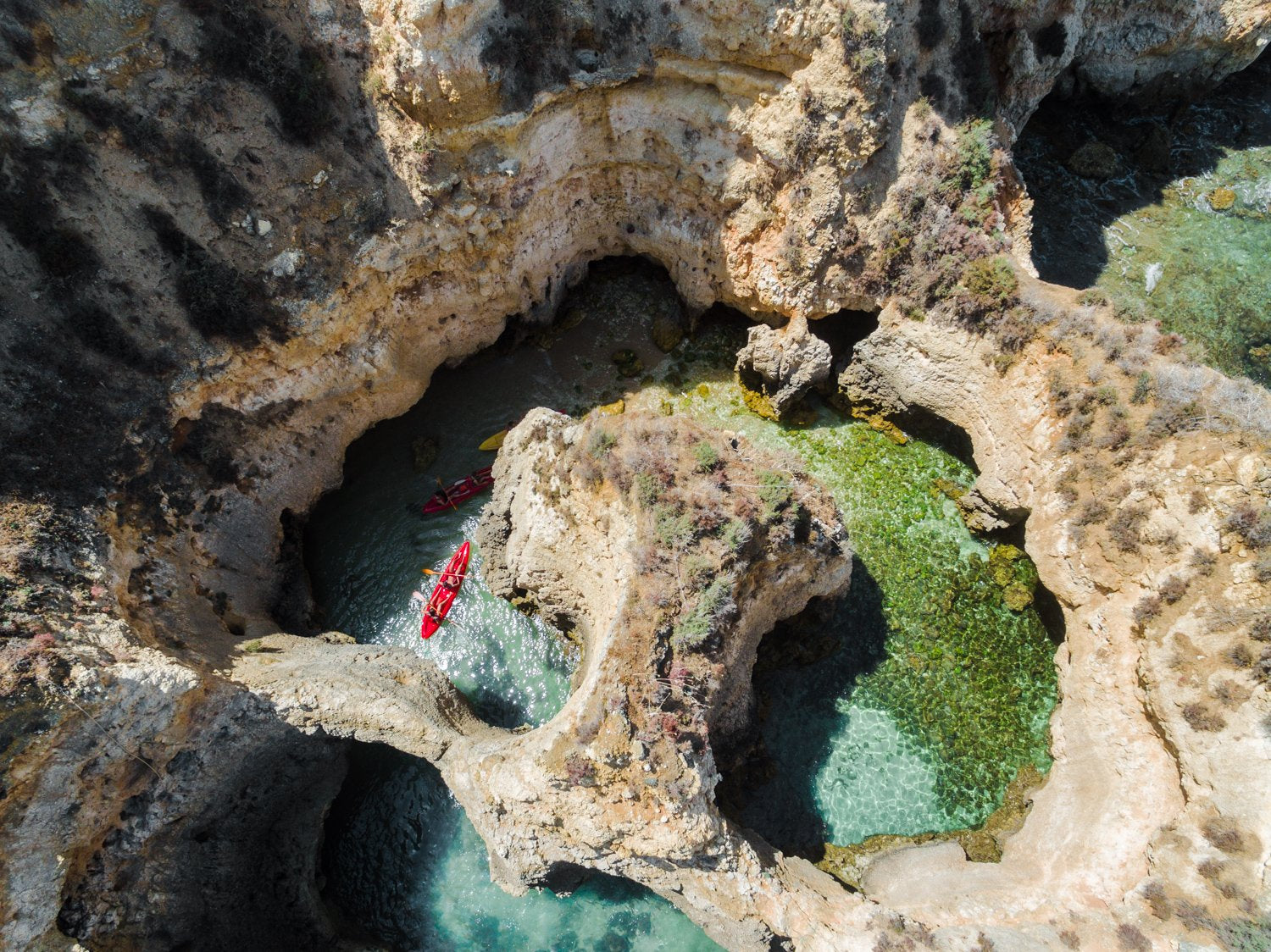 Three kayaks under cliffs and caves in Lagos from the air