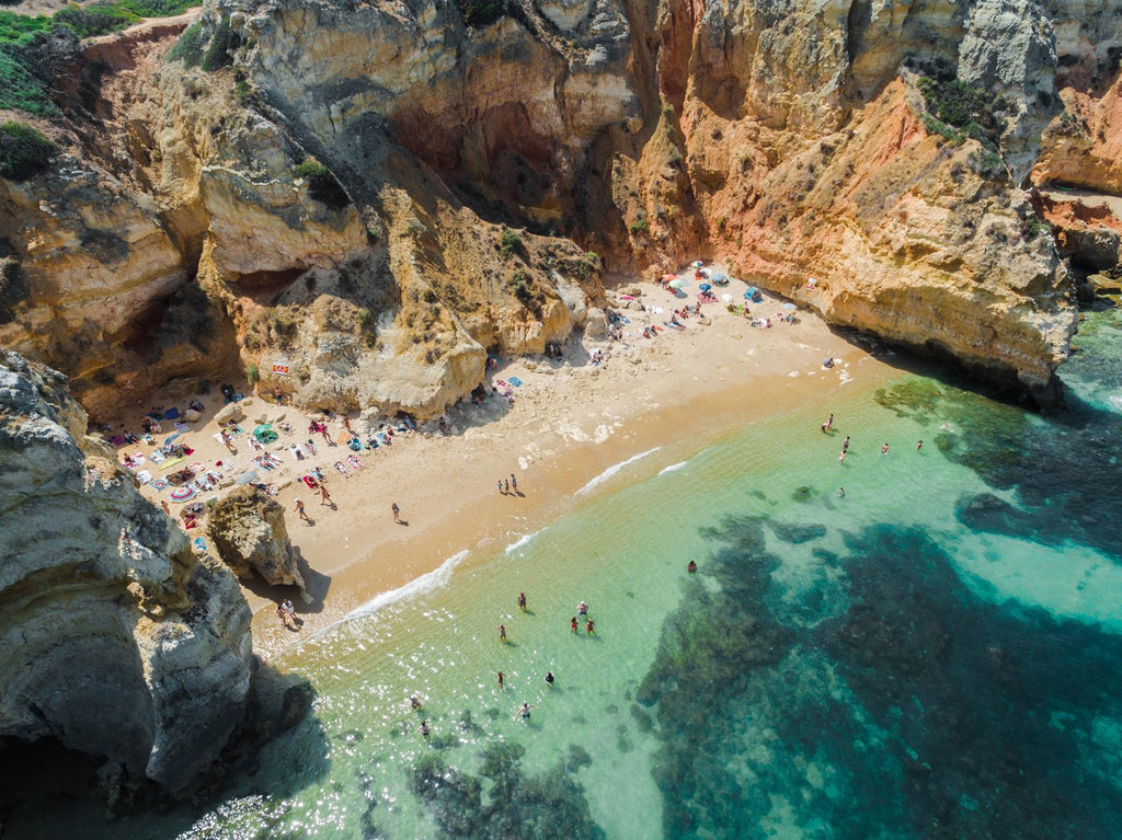 Aerial of clear water and cliffs at Camilo beach in Lagos