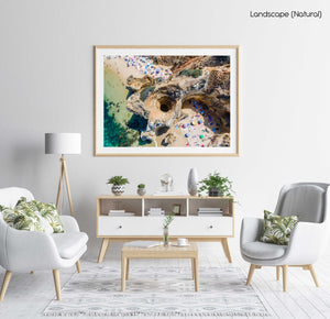 Aerial of a cave tunnel on Camilo Beach in Lagos with people on beach in a natural fine art frame