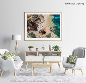 Aerial of beach people near cliffs and cave tunnel on Camilo beach in a natural fine art frame