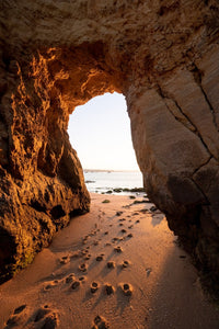 Golden orange light and footsteps through cave at Lagos