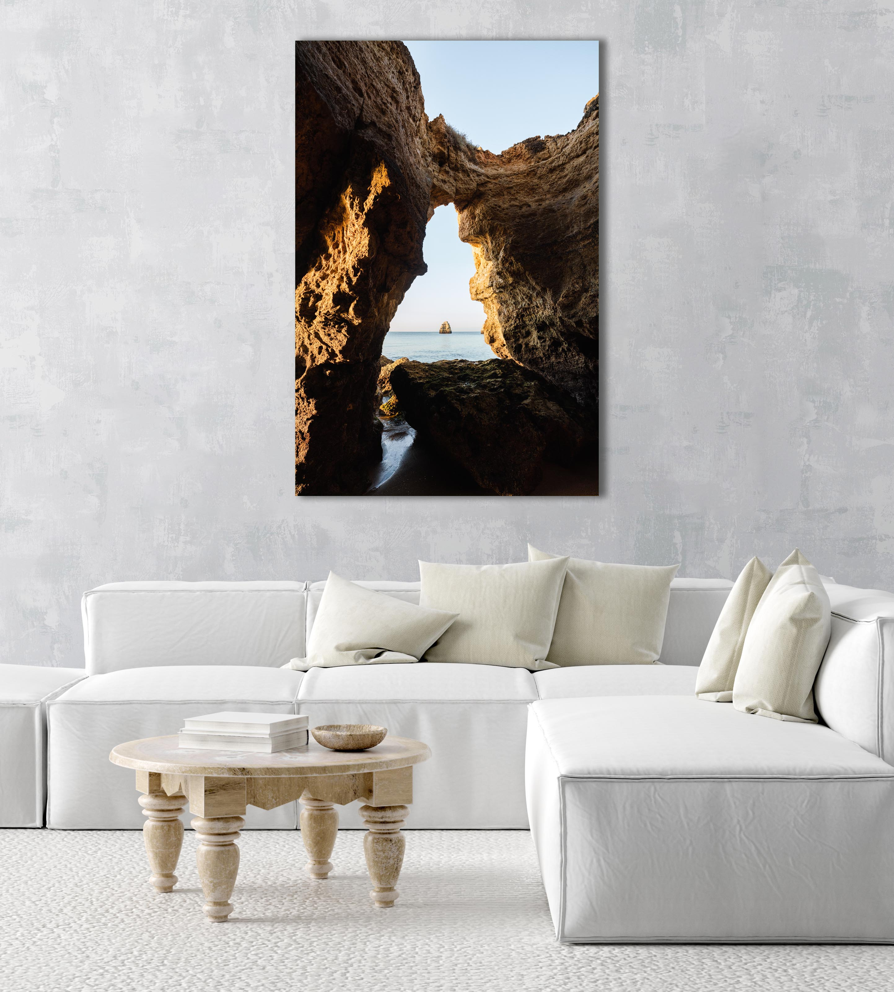 Inside a cave in Lagos looking out to blue sea and rock