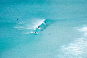 Surfers in Llandudno, Cape Town, on a wave breaking in the middle of blue water.
