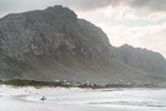 Betty's Bay beach with mountain and surfer