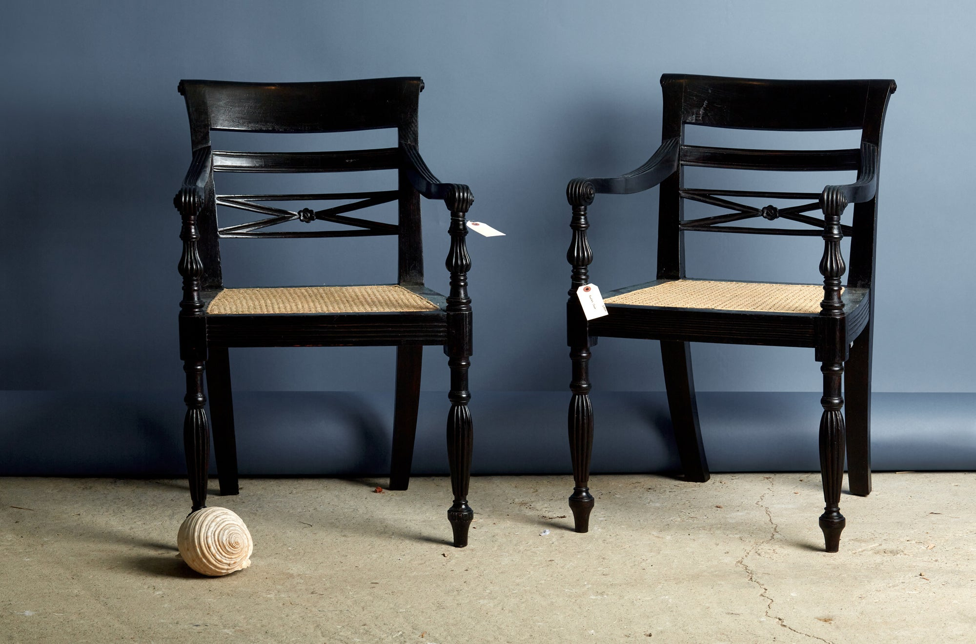 A Pair of Ebonized Teak Cane Seated Raffles Chairs