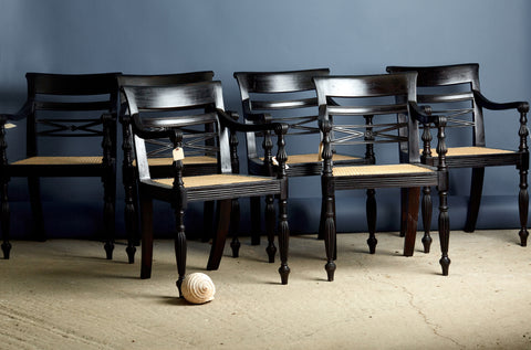 A Set of 8 Ebonized Teak Cane Seated Raffles Chairs