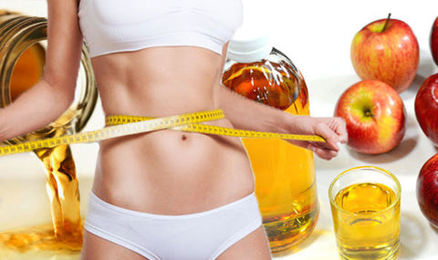 Woman measuring weight after taking apple cider vinegar